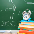 Alarm clock and books against a school board (chemical formulas). — Stock Photo