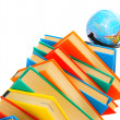 Stock Photo: Globe and pile of multi-coloured books on white background.