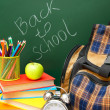 Stock Photo: Back to school. School bag and school accessories against school board.