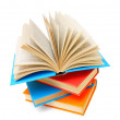 Open book on a pile of multi-coloured books. On a white background. — Stock Photo
