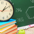 Stock Photo: Watch and books against school board (chemical formulas).