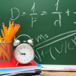 Stock Photo: Alarm clocks and school accessories against school board.