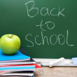 Back to school. An apple and writing-books against a school board. — Stock Photo