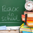 Back to school. An alarm clock and school accessories against a school board. — Stock Photo