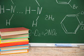 Pile of books against a school board with chemical formulas. — Stock Photo