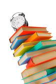 Alarm clock on multi-coloured books. On a white background. — Stock Photo