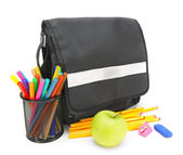 School bag, an apple and school accessories on a white background. — Stock fotografie
