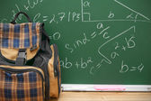 School bag against a school board with mathematical formulas. — Stock Photo
