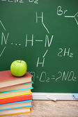 Apple and books against a school board (chemical formulas). — Stock Photo