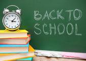 Reloj con alarma y libros contra una junta escolar. regreso a la escuela. — Foto de Stock