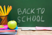 Acessórios Apple e escola contra um conselho escolar. volta às aulas. — Fotografia Stock