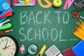 Back to school. Watch, a magnifier and other school subjects against a school board. — Stock Photo