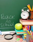 Back to school. An apple, an alarm clock and other school tools against a school board. — Stock Photo