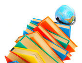 Globe and pile of multi-coloured books on a white background. — Stock Photo