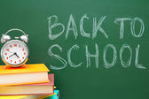 Back to school. An alarm clock and books against a school board. — Stock Photo