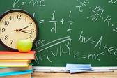 Watch and an apple on books. Against a school board with formulas on the physicist. — Stock Photo