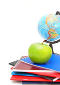 Apple, the globe and writing-books on a white background. — Stock Photo