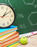 Watch and books against a school board (chemical formulas). — Stock Photo