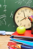 Watch and school accessories against a school board. — Stock Photo