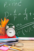 Alarm clocks and school accessories against a school board. — Stock Photo