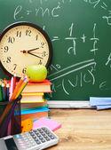 Horloge en andere vakken op school tegen een schoolraad. terug naar school. — Stockfoto