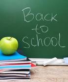Powrót do szkoły. jabłko i zeszyty z kuratorium. — Zdjęcie stockowe