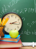 Back to school. Watch, an apple and school subjects against a school board. — Stok fotoğraf