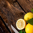 Stock Photo: Lemons and knife. On wooden board.