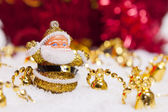 Happy Santa Claus figurine and Christmas golden bells — Stock Photo