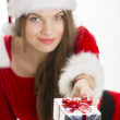 Christmas girl offering gift — Stock Photo