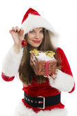 Santa girl holding gift box and red bauble. — Stock Photo