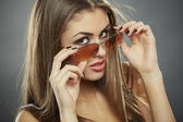 Woman holding sunglasses and looking at you — Stock Photo