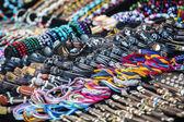Colorful leather bracelets, beads, accessories and souvenirs — Stock Photo