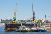 Towboats and cranes in shipyard — Stock Photo
