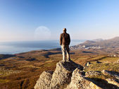 Man on the top of the mountain looking at full moon — Stock Photo