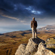 Man on the top of the mountain over cloudy sky — Stock Photo