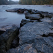 Rocky river bank at foggy morning — Stock Photo