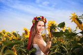 Beautiful young woman with sunflower — Stock Photo