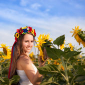 Beautiful young woman at sunflower field — Stock fotografie
