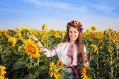 Beautiful young woman at sunflower field — Stock Photo