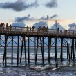 Stock Photo: On Oceanside pier watching waves in afternoon
