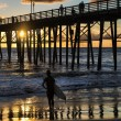 Surfer watching an Oceanside California sunset. - Stock Photo