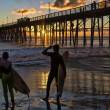 Surfers watch an Oceanside California sunset. - Stock Photo
