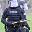 Stock Photo: Show of force - police in riot gear move toward civil unrest