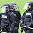 Show of force - police in riot gear move toward the civil unrest - Stock Photo