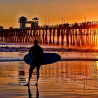 A silhouetted surfer waits for the perfect set - Foto Stock