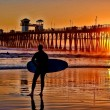 A silhouetted surfer waits for the perfect set - Stockfoto