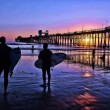 Surfers at sunset in Oceanside, California - Stock Photo
