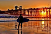 A silhouetted surfer waits for the perfect set — Stock Photo