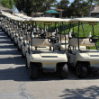 Line of golf carts - several pairs of carts waiting for a game of golf on a clear blue sunny day in Southern California. — Stock Photo